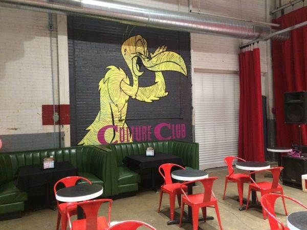 "Full wall mural of a toucan, looking sidelong at the viewer and holding one wing/hand to its mouth. At the bottom of the mural are the words ""Culture Club."" Below the mural are retro green booths, and in front of the booths, red tables and chairs. A stage area is to the right."