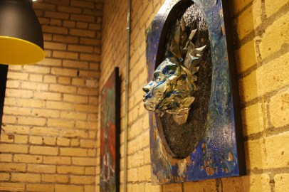 A sculpture of a face hanging on the wall