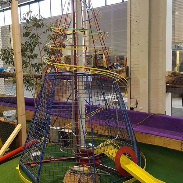"""The Comet"" is a conical structure of wire and tubes, featuring a nine foot Archimedes screw in the center. The golf ball is carried up the to the top of the cone, and then released down a series of winding tracks and tubes, before shooting out a slide at the base. Rube Goldberg-esque."