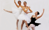 Three women dancers, two in white tutus and a third in black.