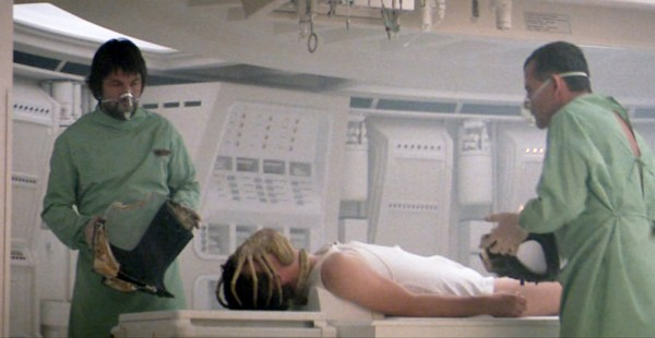 Dallas (Skerritt), and Ash (Ian Holm), try to administer to Kane (John Hurt) as he's being orally inseminated.