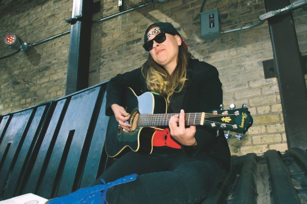 A woman sits on a dumpster, holding a guitar. She is wearing a backwards baseball cap and sunglasses. She strikes a pose, nodding at the camera, while preparing to play the guitar.