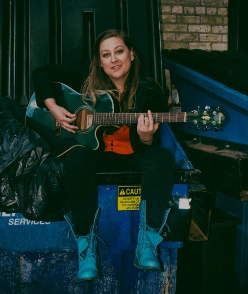 A woman sits on a dumpster, wearing cowboy boots and holding a guitar. She looks directly into the camera while preparing to play a song on the guitar.