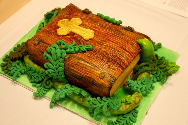A cake designed to look like a Bible with leaves and a snake around it