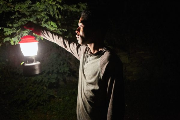 Travis in the woods, shining a lantern into the darkness.