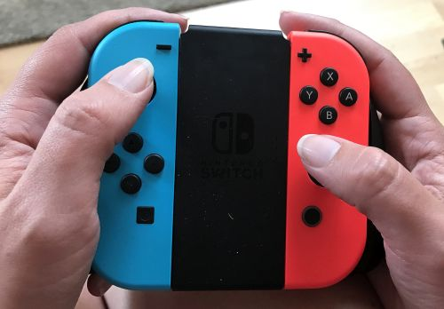 Adult Hands holding a pair of Joy-Con controllers