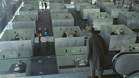 Mr. Hulot looks over a cubicle farm.