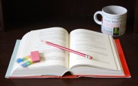 A book, coffee cup, and writing tools