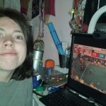 A brunette midlength haired person with a grey sweater watching robots on a field on a computer.