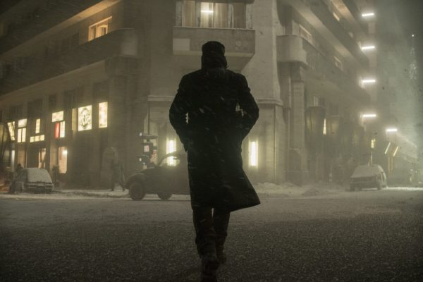 Officer K in a trench coat approaching a building on a dark, snowy night.