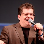 Photo of Patton Oswalt on a stage with a microphone
