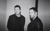 Atticus Ross and Trent Reznor look to the camera with straight expressions, the photo is black and white