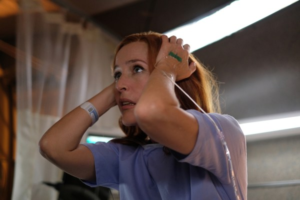 Scully with her hands on her head