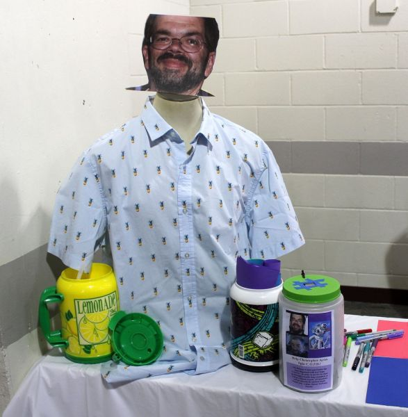 A picture of Chris Ayres wearing a shirt, along with a donation container