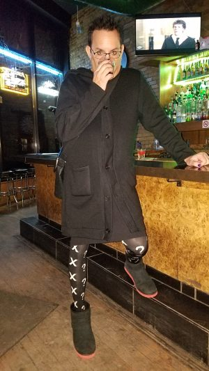 Trace standing at a bar in a kilt and tights