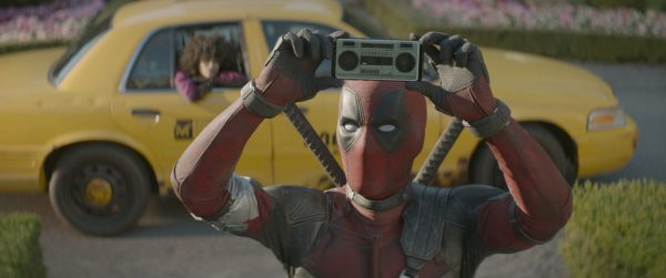 Deadpool holding up a tiny boombox