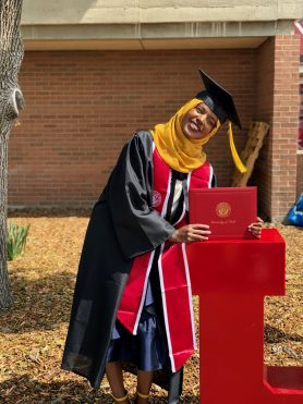 Abdi poses for a photo in her commencement gown with her diploma.