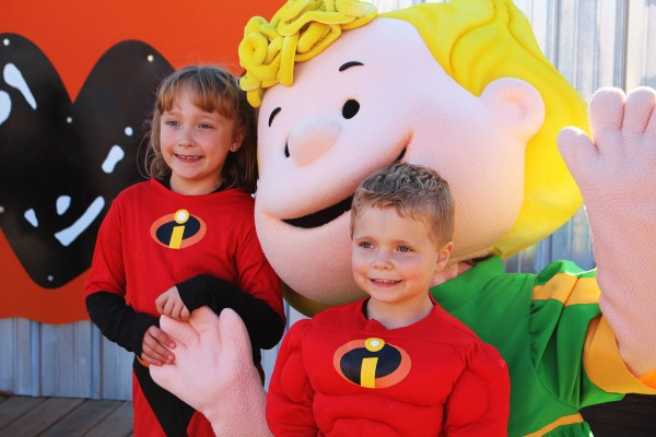Two kids in costume with Peanuts characters