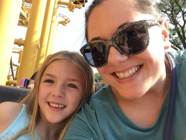 Rae and her daughter pose for a selfie on a roller coaster.