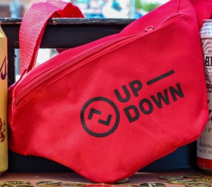 "A red fanny pack bearing the words ""Up-Down"" and the bar's logo, in between two beer cans."