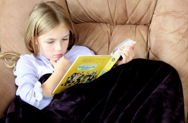 A girl curled up in a chair reading a book.