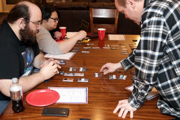 Players sit at a table with cards in out in front of them, learning how combat works in Seize the Imperium.