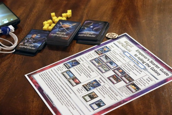 Decks of cards and yellow playing pieces sit alongside Imperium's Emperor's Starter Guide to ruling the Galaxy (the rules).