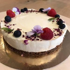 witte cheesecake met bloemen en fruit afwerking
