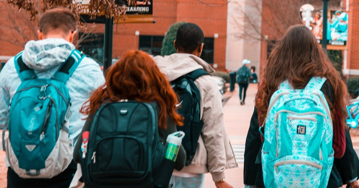 secondary school students walking with backpacks