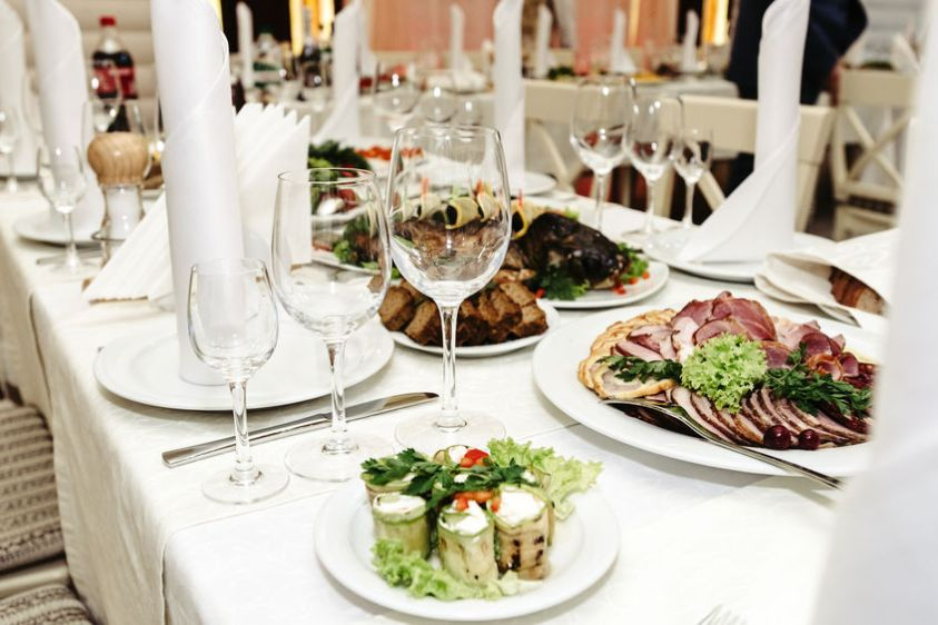 stylish fashionable decorated table with glasses and delicious food, celebration wedding, catering in the restaurant
