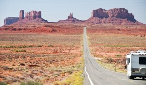 RV driving down the road in monument valley