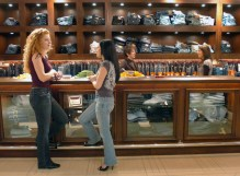 Gloss employee Whitney Cather, left, talks to patron Danielle Chrysogelos during a jean party at the new store, January 20, 2008, in Colorado Springs, Colorado. There is a bar at the store so customers can enjoy a glass of wine while trying on jeans. (Jerilee Bennett/Colorado Springs Gazette/MCT)