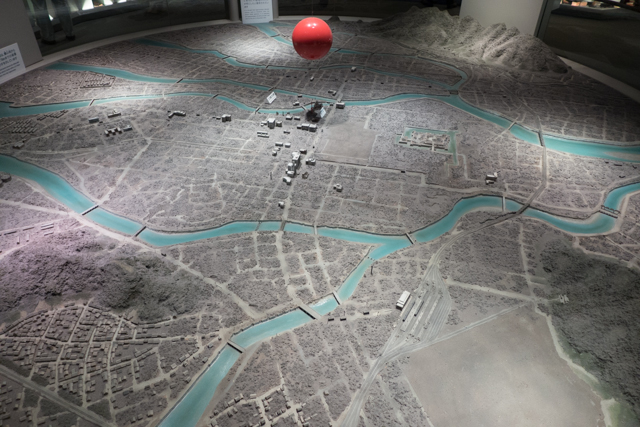 A model depicting Hiroshima right before the bomb was detonated.  The diameter of this model represents a distance of about 3 miles.  The bomb was detonated at the point of the red sphere.  On this scale, the bomb would be about 1/100 of an inch.