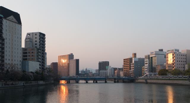 The buildings glow from the sunset along one of the many rivers that flow through Hiroshima.