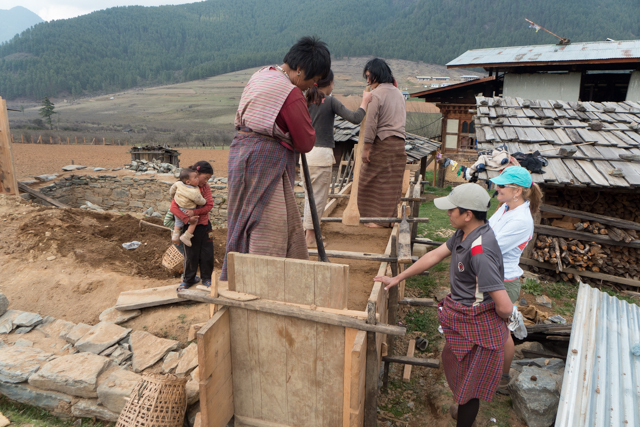 Building a house in Bhutan - the women are pounding mud into a rectangular wooden frame to build the walls of a new house. The harder they pound the mud, the stronger the house will be.   Hard work to say the least.  The thick mud walls retain heat in the winter and repel heat in the summer.