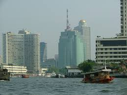 Emerging from the canals into the wider river, modern Bangkok ahead.