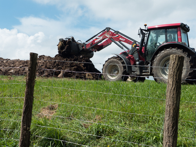 This tractor is spreading manure into this pasture.  We smelled it about 200 yards before we saw it.