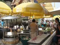 Em frente ao templo do Buda de Esmeralda devotos deixam oferendas