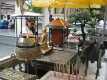 Os budistas pregam pedaços de papel dourado nas estátuas que ficam por ali
