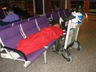 Carlos dormindo no aeroporto. Eu também dormi. Cobertor da Dragon Air.