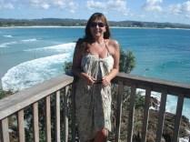 Atrás de mim, além dos surfistas, a praia de Byron Bay