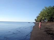 Caroline posando na praia. As praias do Taiti são vulcânicas e de areia negra