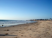 Praia grande, fria e de areia escura