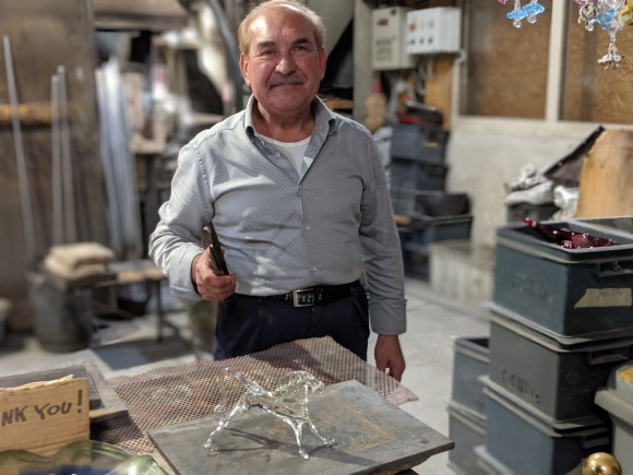 Man with glass horse on the island of Murano, a product of glass blowing in Murano, Italy