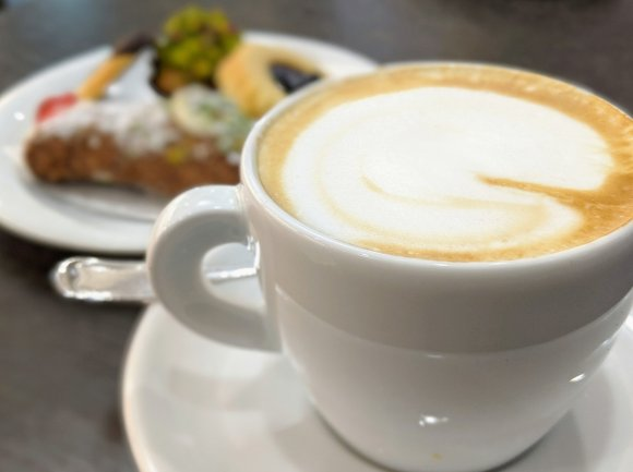 Cup of cappucino with pastry in background