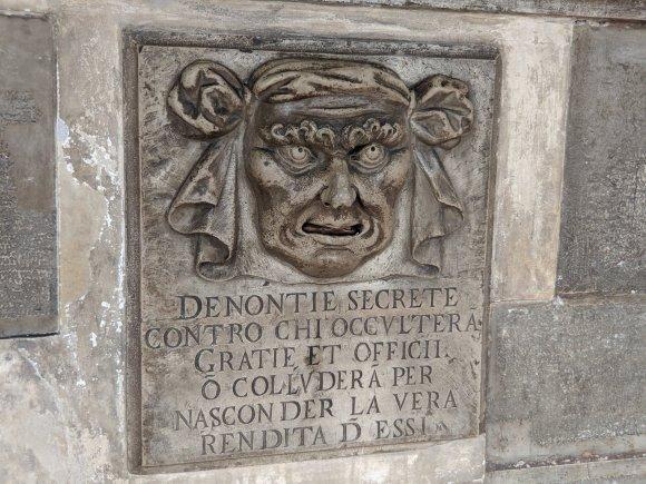 Stone carving of a face mounted in a stone wall at the Doge's Palace, Venice, Italy
