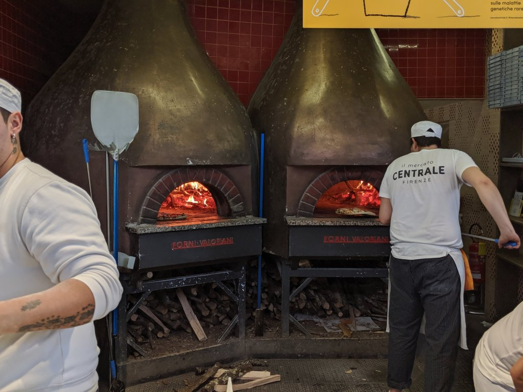 Two men in front of brick pizza ovens at the Mercato Centrale in Florence, Italy