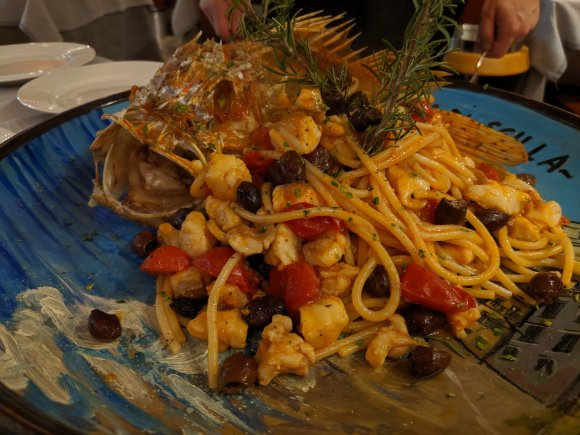 Red snapper next to fish and pasta dish
