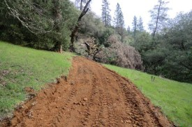 freshly graded earthen road along the side of a hill