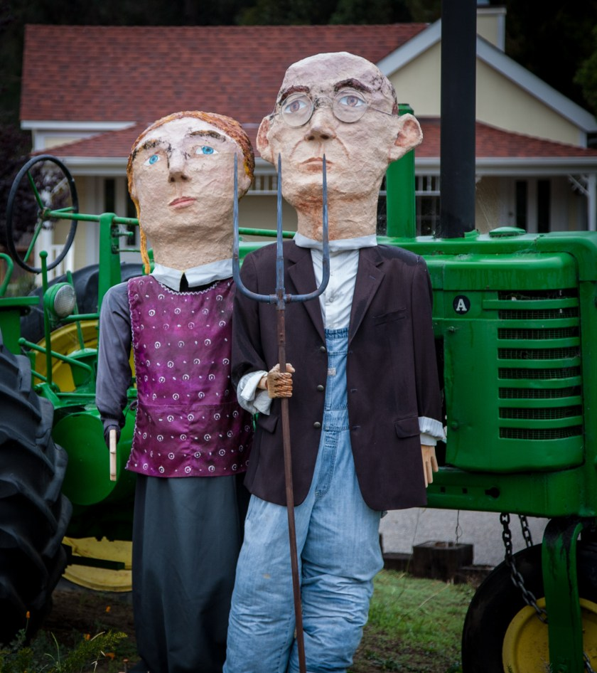 """Depiction of Grant Wood's """"American Gothic"""" with paper mache characters in front of a john deere tractor and midwestern farm house"""